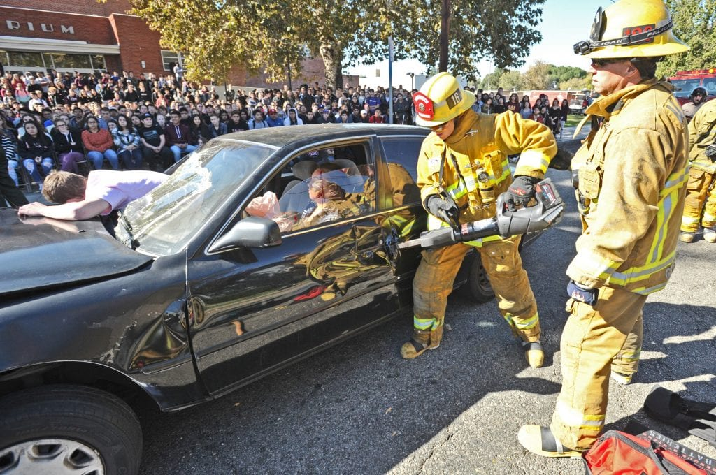Firefighters use the jaws of life as they demonstrate the process of extracting a person from a car in front of 1200 Hart High School junior and senior students during the Every 15 Minutes presentation held in front of Hart High School in Newhall on Thursday. Dan Watson/The Signal