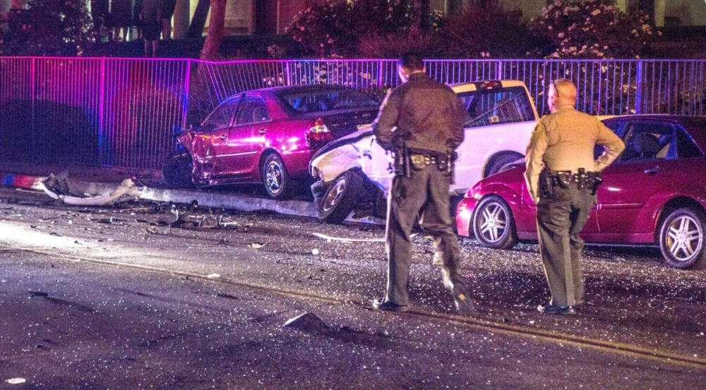 Santa Clarita Valley Sheriff's Deputy surveys damage to mulitple cars. Photo by Austin Dave.