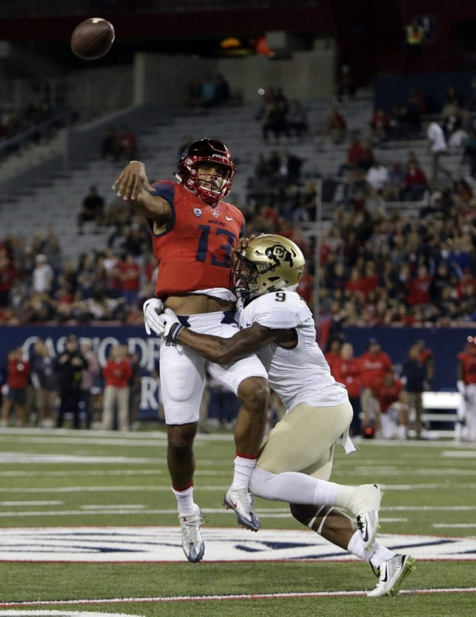 Arizona quarterback Brandon Dawkins (13) throws off balance while being pressured by Colorado defensive back Tedric Thompson during the first half of an NCAA college football game, Saturday in Tucson, Ariz. (AP Photo/Rick Scuteri)