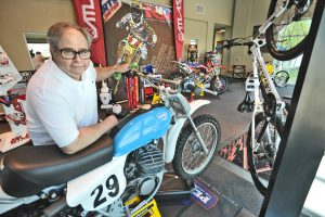 Eddie Cole, President of Matrix Concepts with the 1971 vintage Penton Motorcycle he used to ride which is displayed in the lobby of Matrix Concepts in Valencia. Dan Watson/The Signal