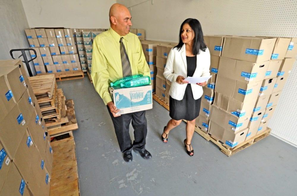 Pramesh Sharma, left, and Mala Sharma discuss their products in the Island Blu Water warehouse in Valencia. 101316  Dan Watson/The Signal