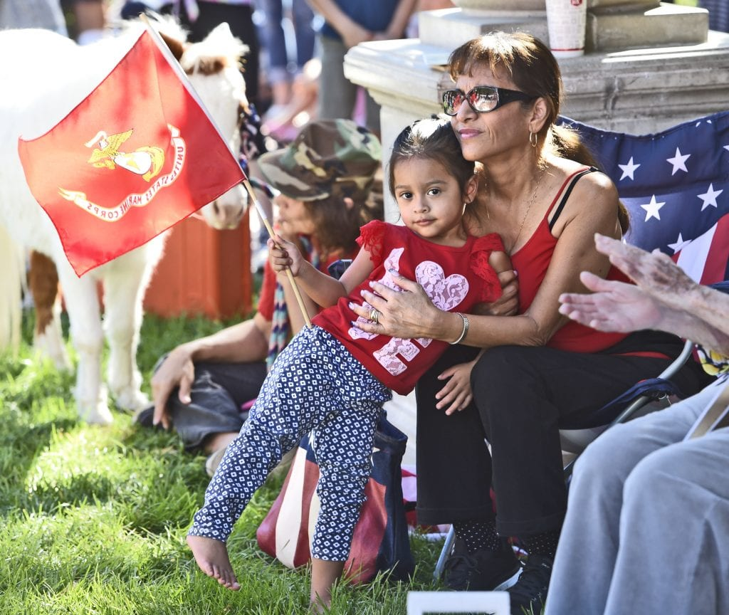 Irene Chavez, right, hugs Gigi Nava, 2, as she waves the flag of the U.S. Marine Corps as they join hundreds who attended the annual Veterans Day Ceremony held at Veteran's Historical park in Newhall on Friday. Dan Watson/The Signal