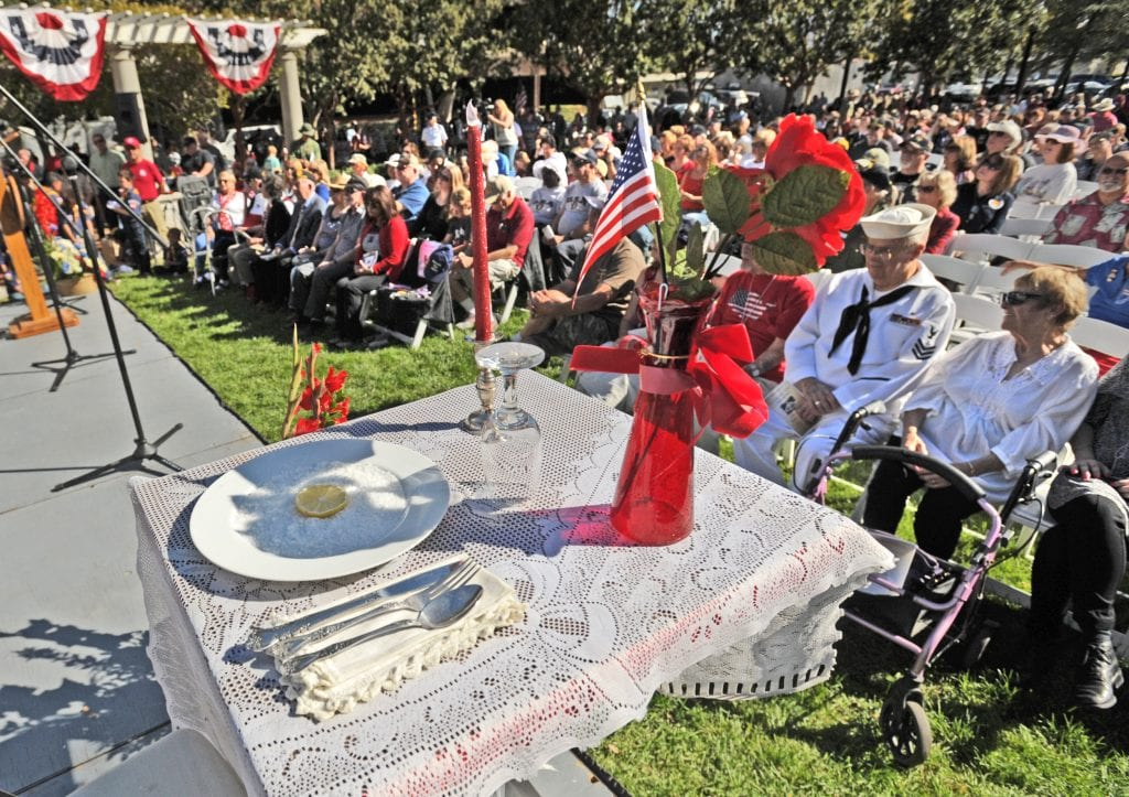 An empty place setting stands on stage in honor of the MIA and POWs as hundreds attend the annual Veterans Day Ceremony held at Veteran's Historical Park in Newhall on Friday. Dan Watson/The Signal