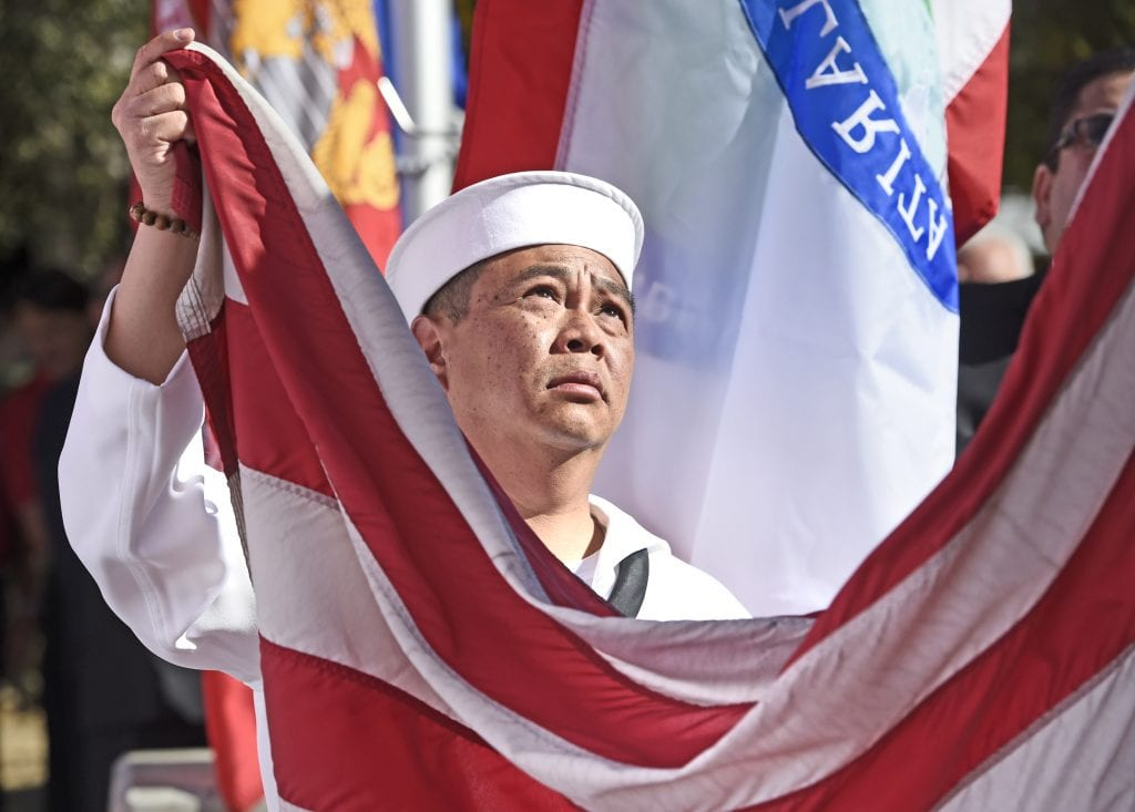 U.S. Navy veteran Steve Quach helps to lower the American flag that will be retired during the changing of the flags ceremony at the Veterans Day Ceremony held at Veteran's Historical Park in Newhall on Friday. Dan Watson/The Signal