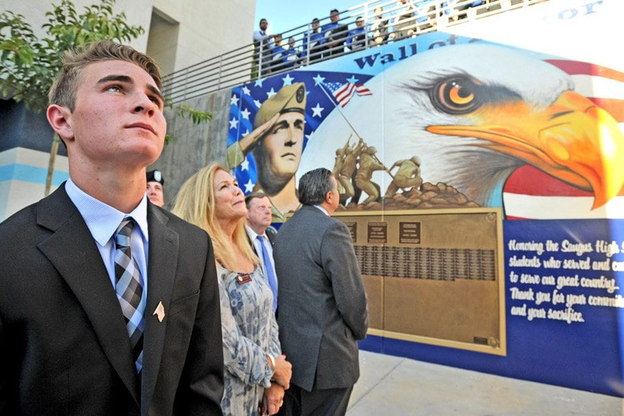 Saugus High School student Steven Plante, left, who spear-headed the Saugus High School Wall of Honor project, behind him, listens to the Saugus Concert Choir as they sing God Bless America after the unveiling of the Wall of Honor at Saugus High School on Friday. Dan Watson/The Signal