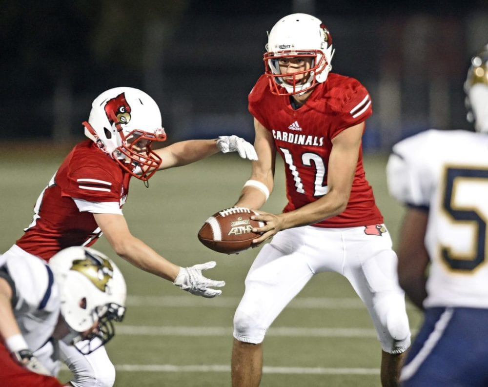 Santa Clarita Christian School's Lucas Pettee (25), left, takes a handoff from SCCS quarterback Tristan Miller (12)  against Campbell Hall at Canyon Country.  Signal photo/Dan Watson