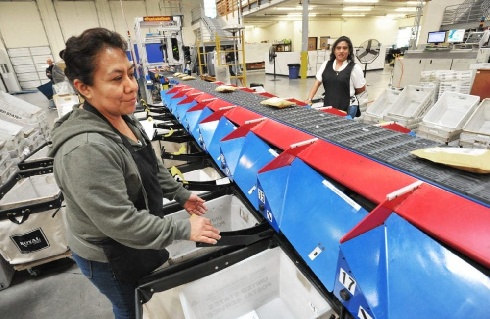 Machine operators Jackie Benito, left, and Ana Martinez work at the automated parcel sorter in the 35,000 square foot Postage One production plant in Valencia. Dan Watson/The Signal