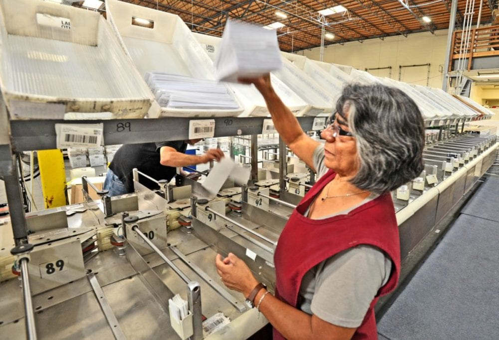 Machine operator Margarita Martinez works at the automated letter sorter in the 35,000 square foot Postage One production plant in Valencia. Dan Watson/The Signal