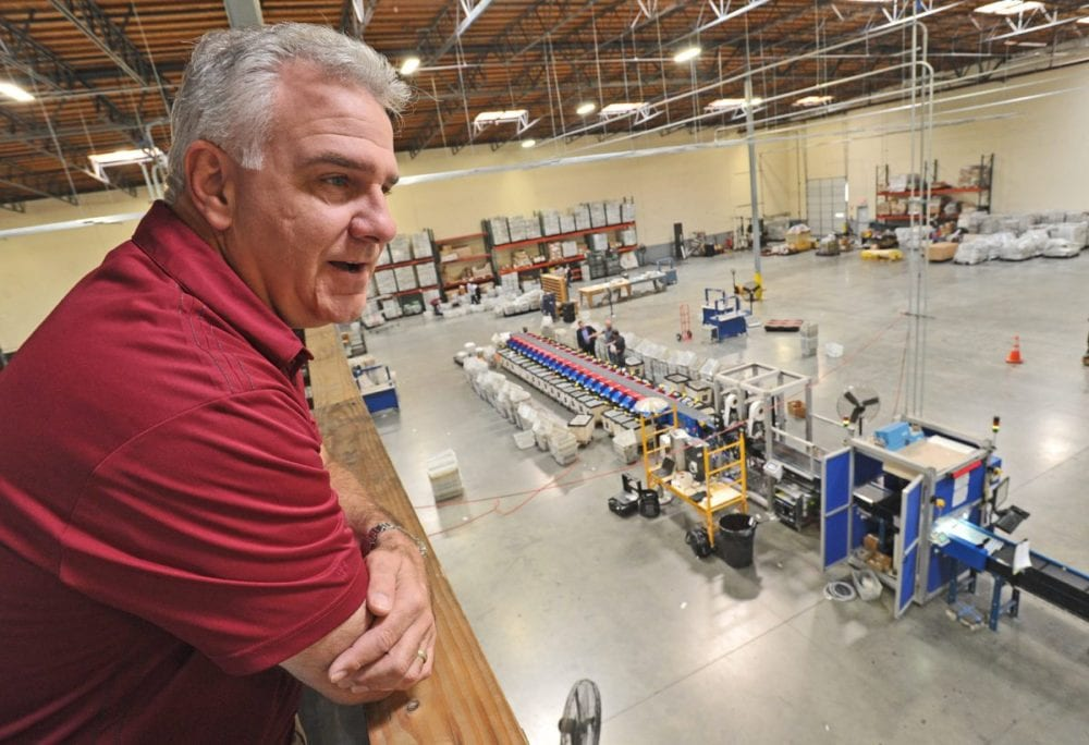 Postage One President and CEO Jeff DeVico overlooks the 35,000 square foot production plant in Valencia. Dan Watson/The Signal