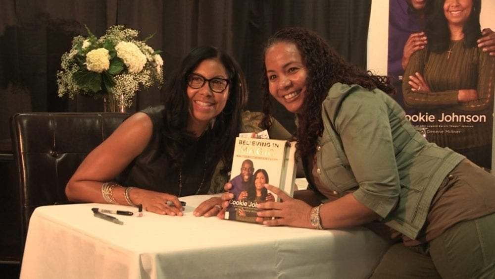 Cookie Johnson poses with an attendee at a book signing held at Albert Einstein Academy in Valencia on Sunday.