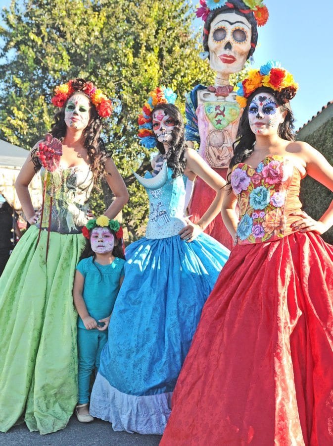 Daniella Mendoza, 3, second from left, poses for her mother to take a picture of her with three women dressed in costume as La Catrina at the annual Dia de los Muertos festival held at Eternal Valley Memorial Park in Newhall on Saturday. Dan Watson/The Signal