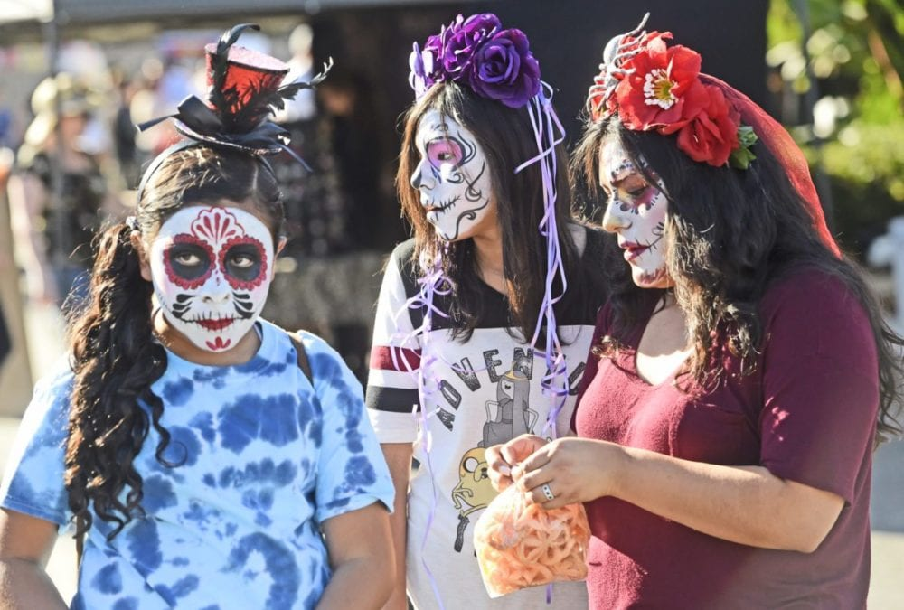 From left, Natalie and Claudia Meza and Jessica Lopez enjoy the festivities after getting their faces painted at the annual Dia de los Muertos festival held at Eternal Valley Memorial Park in Newhall on Saturday. Dan Watson/The Signal