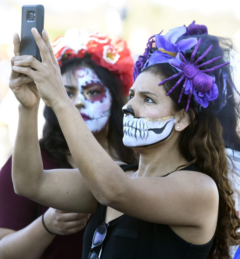 Ana Rojas, right, takes a picture othe entertainment on stage at the annual Dia de los Muertos festival held at Eternal Valley Memorial Park in Newhall on Saturday. Dan Watson/The Signal
