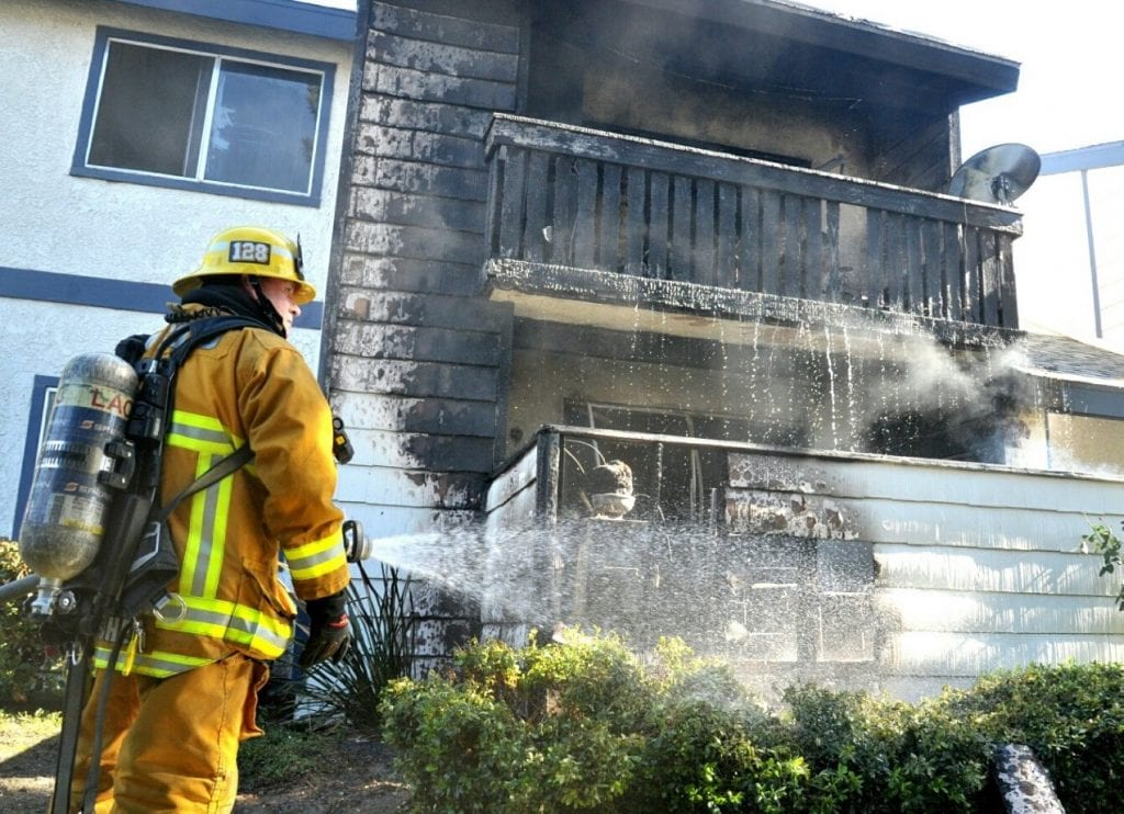 A fire fighter douses the scene of an apartment fire on Haskell Canyon Road Saturday afternoon. Dan Watson/ The Signal