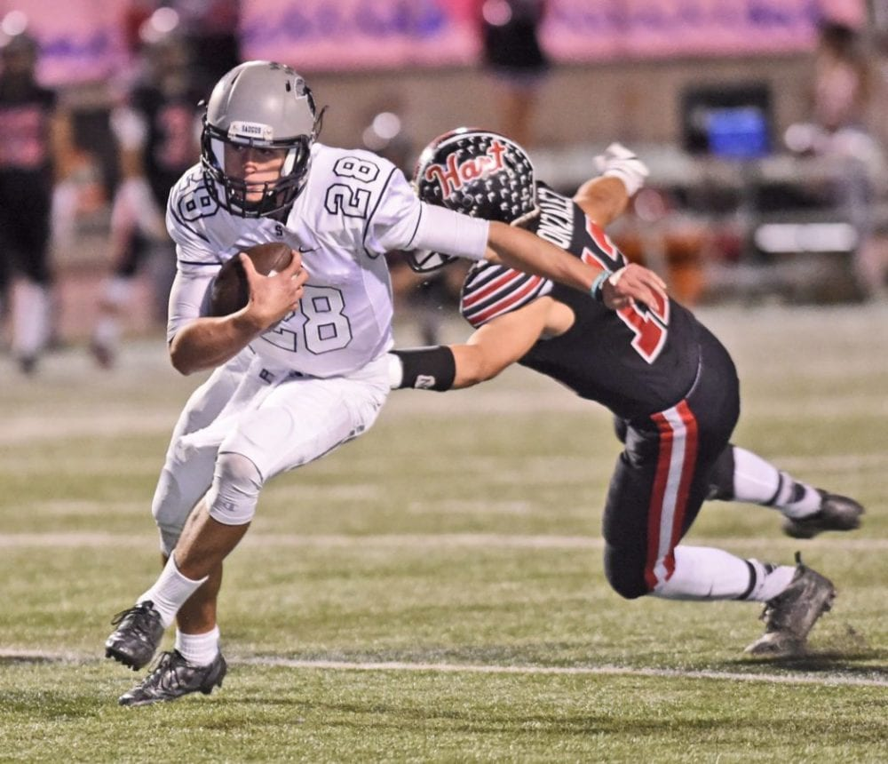 Saugus quarterback Nathan Eldridge (28) evades Hart defender Vincent Gonzalez (12) at College of the Canyons on Friday.  Dan Watson/The Signal