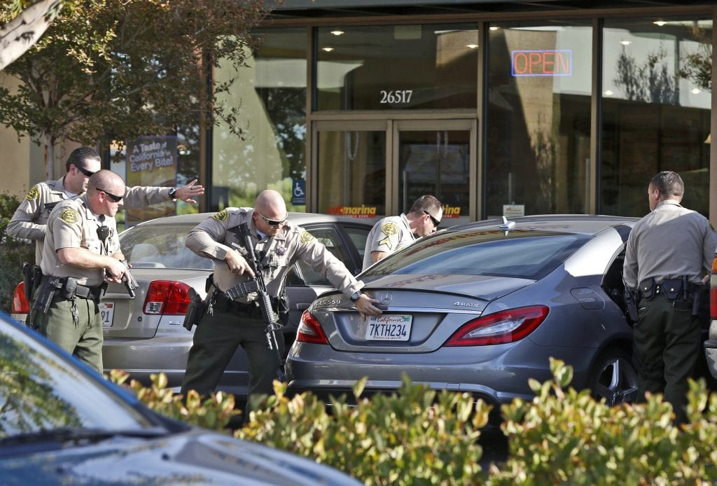 Sheriff's deputies approach a vehicle in front of GameStop on Friday after three males were instructed to exit the vehicle and detained at gunpoint. Katharine Lotze/Signal