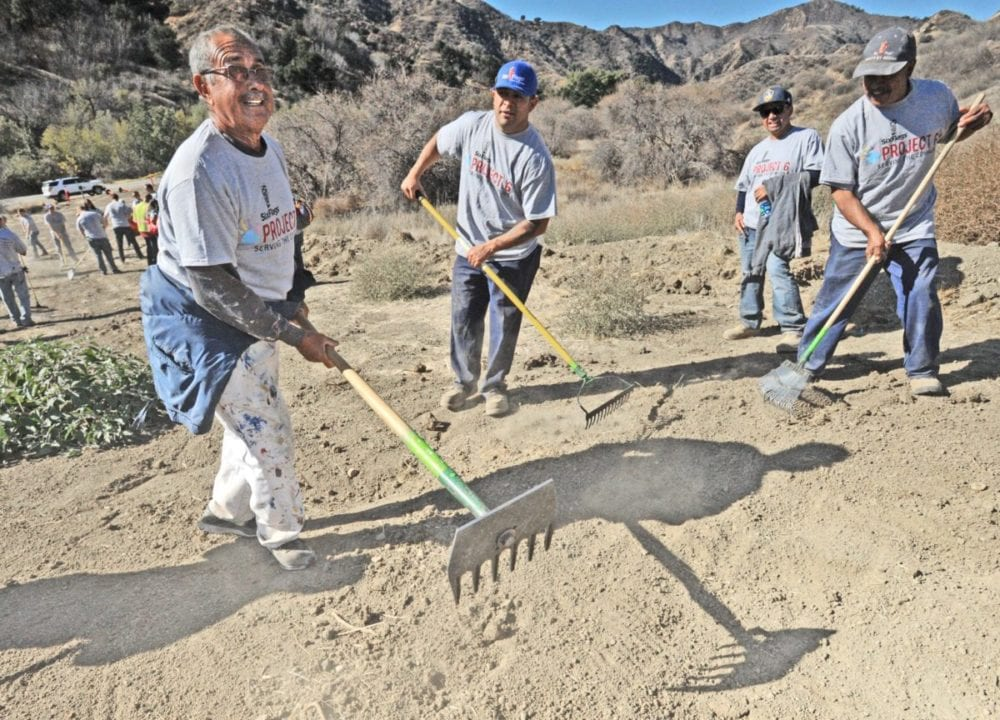 Field painter Hector Lepe, left,  joins more than 30 Six Flags Magic Mountain employees as they  prepare the soil for a mixture of sixteen native seeds to be planted an area of the Taylor Open Space at Rivendale Park near Towsley Canyon Park in Newhall on Thursday.   Ninety acres of the open space burned  in the Sage Fire in July of 2016.   Two hundred Six Flags Magic Mountain employees worked at  planting new vegetation at three Santa Clarita burn locations as part of the company's  annual Day of Service aimed at improving the overall quality of the community.  Dan Watson/The Signal