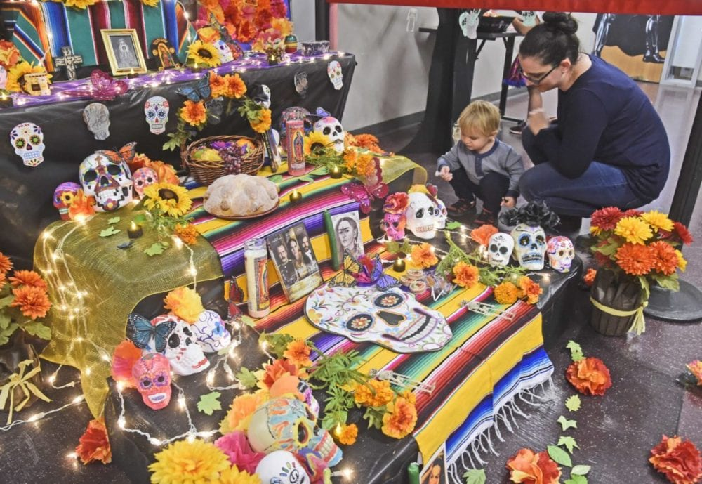 Michael Capella, 2,  left, and his mother, College of the Canyons student, Diana Capella take a close-up lokk at the Day of The Dead alter on display at the inaugural  Day of the Dead event  held at Mentry Hall at College of the Canyons in Valencia  on Tuesday. Dan Watson/The Signal