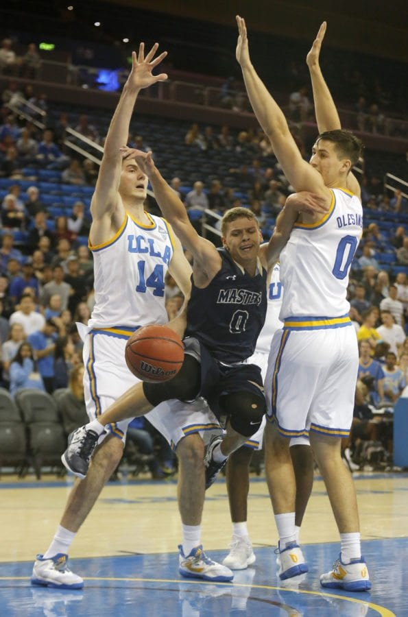The Master's University's Hansel Atencia (0) is sandwiched between UCLA's Gyorgy Goloman (14), left, and Alex Olesinski (0), right, as he went in for a layup during an exhibition game at Pauley Pavilion in Los Angeles on Tuesday. Katharine Lotze/Signal