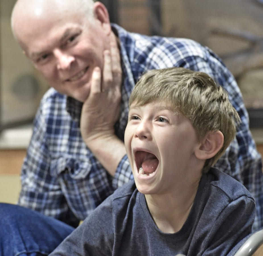 Adrian Tester, left, looks on as Christian Tester,7, opens his mouth as he can to mimic a snake preparing to eat a mouse during the weekly Native Live Animal Presentation at the Placerita Canyon Nature Center on Saturday. Dan Watson/The Signal