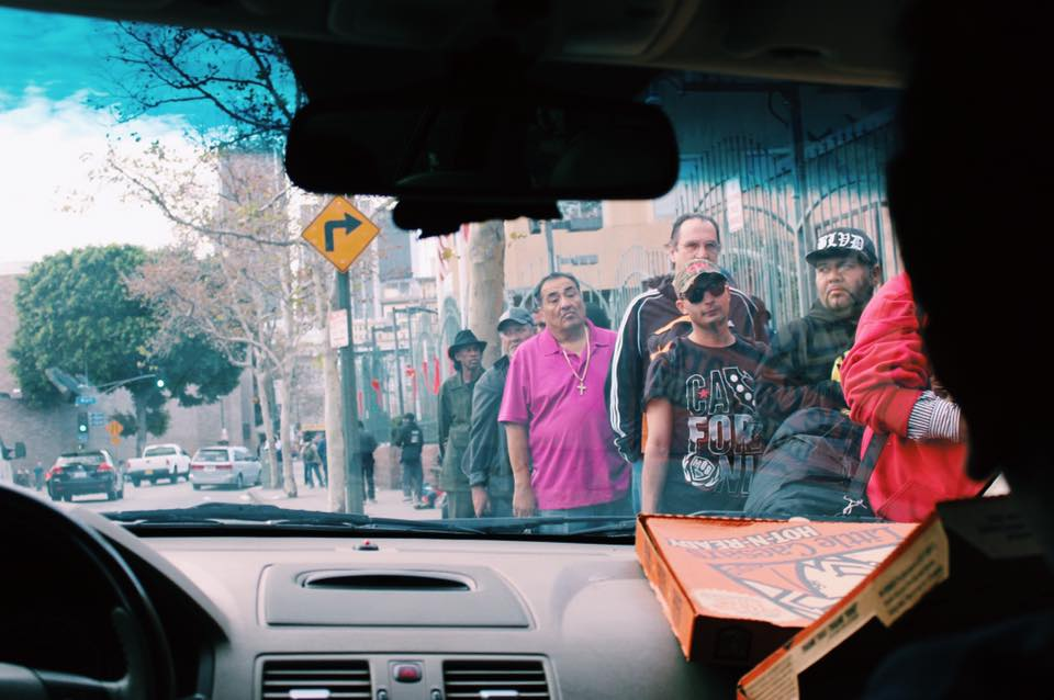 Homeless people living on the streets of downtown Los Angeles line up to receive supplies from Project Pizza on December 20. Courtesy photo