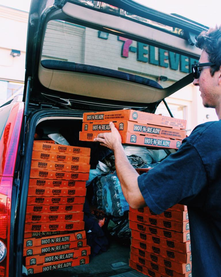 Devin Guggenheimer, 19, loads up his car with 45 pizza boxes of Little Caesars Pizza to pass out to the homeless on the streets of Downtown Los Angeles on December 20. Courtesy photo