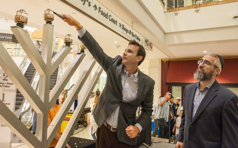 Santa Clarita Mayor Cameron Smyth (L) lights the menorah as Rabbi Choni Marozov (R) from Chabad of Santa Clarita Valley looks on during a Chanukah celebration at the Westfield Town Center. Photo Tom Cruze/For the Signal