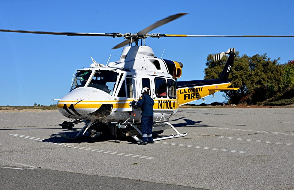 An infant who fell into a Stevenson Ranch pool is loaded into a fire department helicopter in an abandoned parking lot Wednesday. Rick McClure/For The Signal
