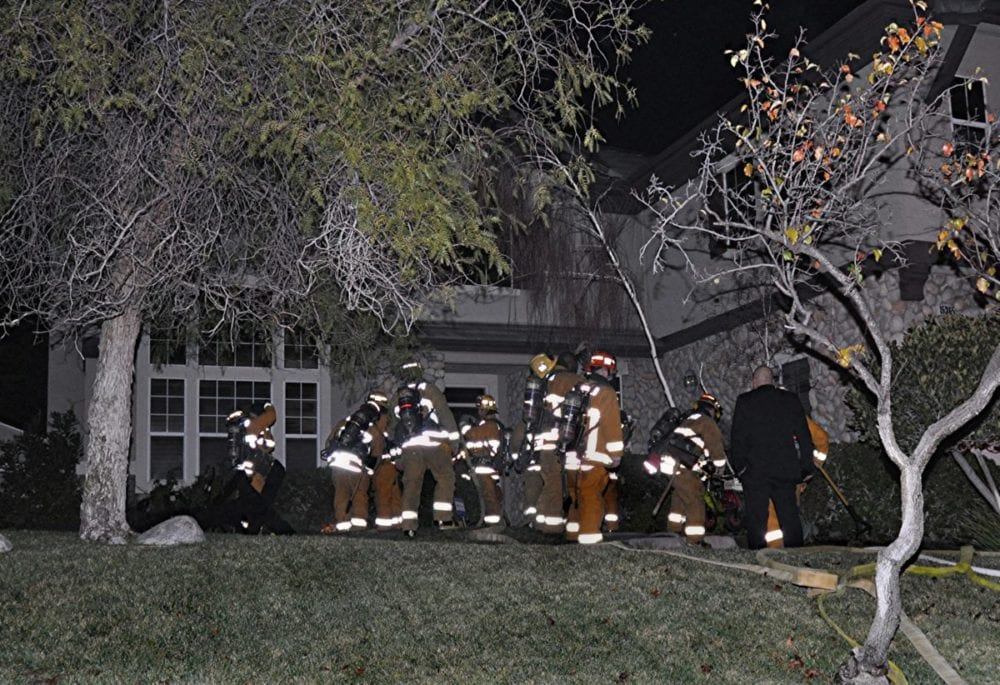 Los Angeles County firefighter put out flames of a Santa Clarita house shortly after 2 a.m. Sunday. Photo by Rick McClure, for the Signal