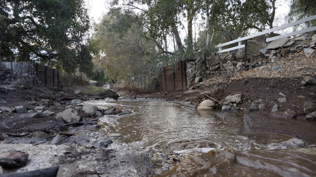 Water, mud and debris flows downhill in a trench along Iron Canyon Road on Sunday after Friday night's storm causes mudslides in the Sand Canyon areas. Samie Gebers/ The Signal