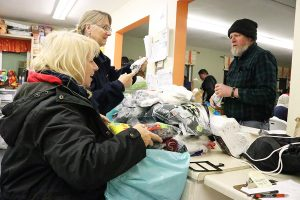 Carolyn Odien, left, and Sheila Wyeth prepare clothes that are available for the homeless to pick up at Bridge to Home's winter shelter on Drayton Street in Santa Clarita on Christmas Eve. Nikolas Samuels/The Signal