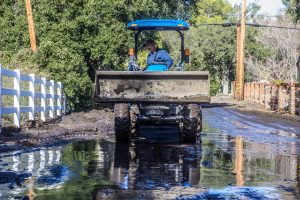 A man uses a skip loader to shift mud off Josel Drive near Iron Canyon Road in the Sand Canyon area of Santa Clarita Saturday afternoon. Austin Dave/Signal