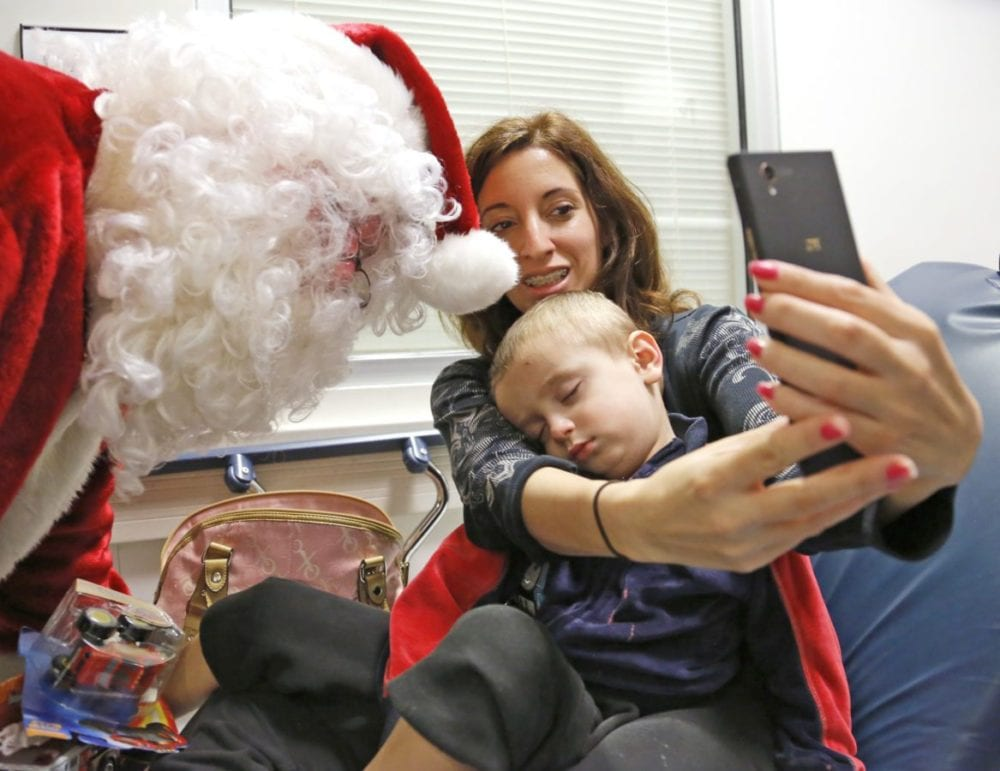 Franny Marshall takes a selfie with Santa as son Cayden, 2, sleeps in her arms during a visit to the Henry Mayo Emergency Department on Thursday. Santa visited children in the emergency room to hand out presents, with the help of Zach's Miracle. Katharine Lotze/Signal