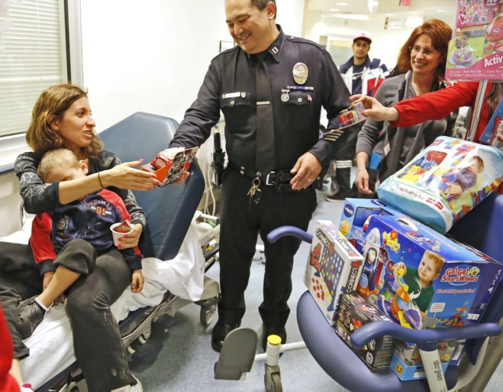Franny Marshall picks out a gift for her son, Cayden, 2, as he sleeps during a visit to the Henry Mayo Emergency Department on Thursday. Santa dropped by the emergency room to visit with kids and bring gifts, with help from Zach's Miracle. Katharine Lotze/Signal