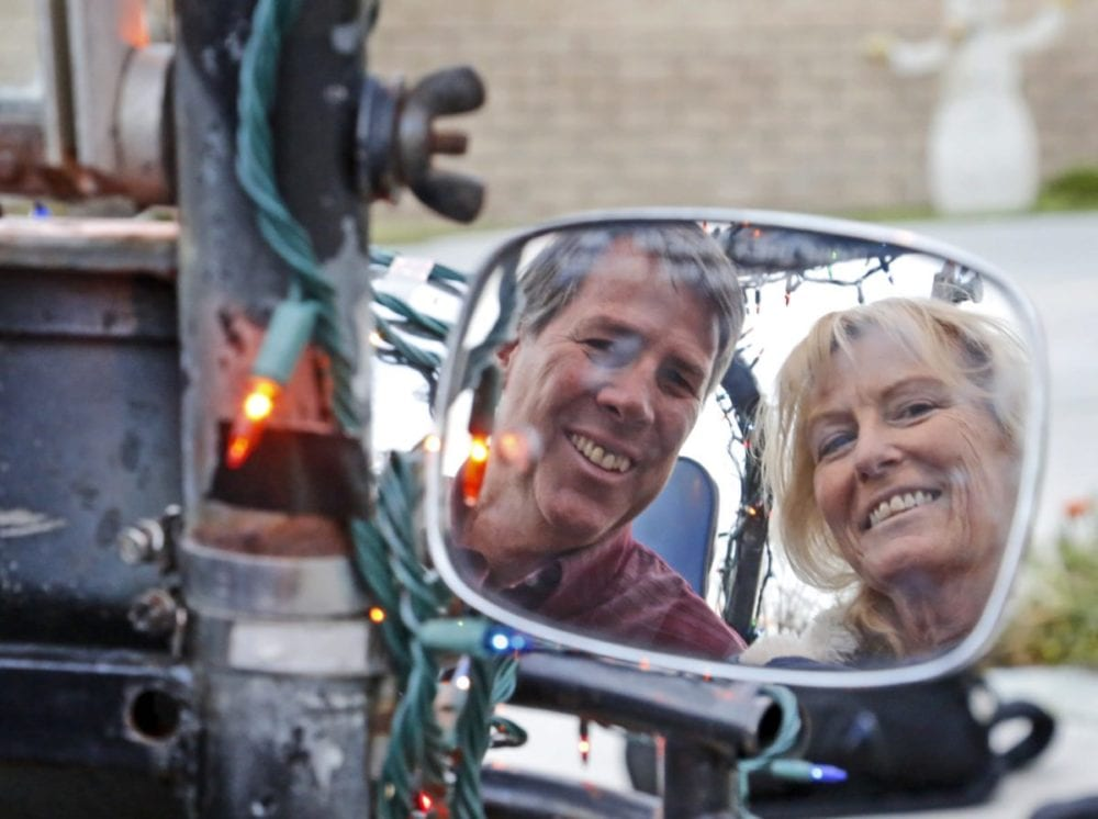Keith and Mary Williams smile as they're reflected in the side mirror of their lighted dune buggy in front of their Valencia home. Katharine Lotze/Signal