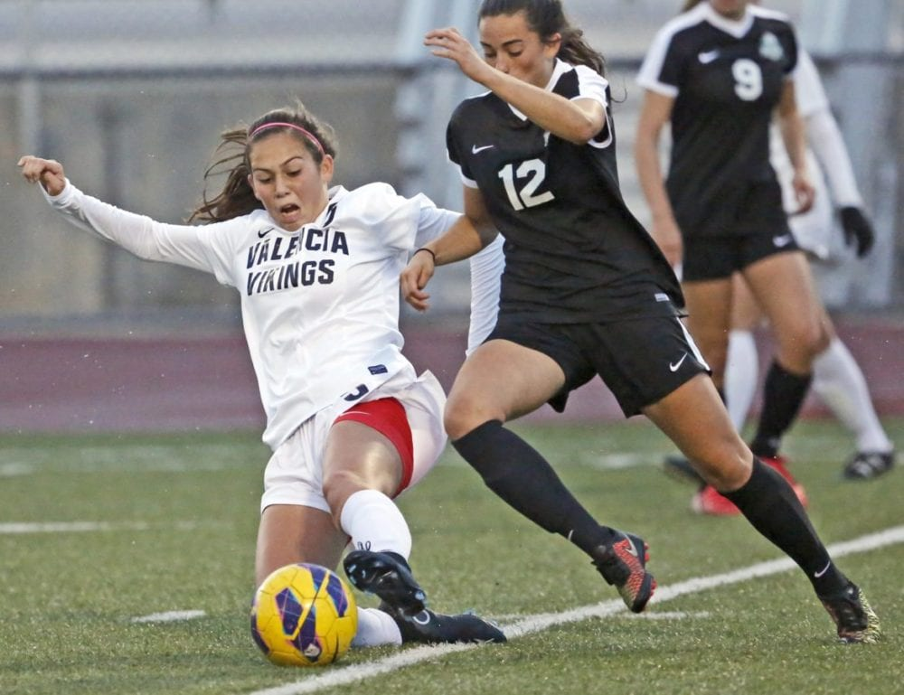 Valencia's Kianna Kukaua (5) slides to keep Granada Hills Charter's Cordelia Cross (12) from stealing the ball during a soccer game at Valencia on Wednesday. Katharine Lotze/Signal