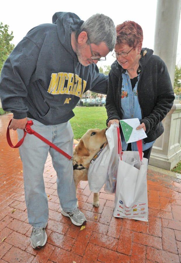 West Ranch High School Cafeteria Manager Koral Newman, right, presents a check, snacks and dog treats to United Sates Marine Corps veteran Dominic Macaya and his service dog, Kyle at Veterans Historical Plaza in Newhall on Wednesday. Dan Watson/The Signal