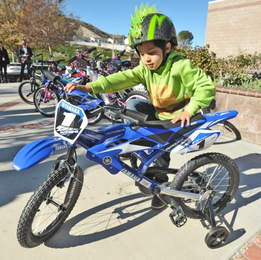 Andrew Peralta, 4, wearing his new bike helmet, makes his pick from the 39 bicycles donated by Chiquita Canyon to the Child & Family Center in Santa Clarita on Tuesday. Dan Watson/The Signal
