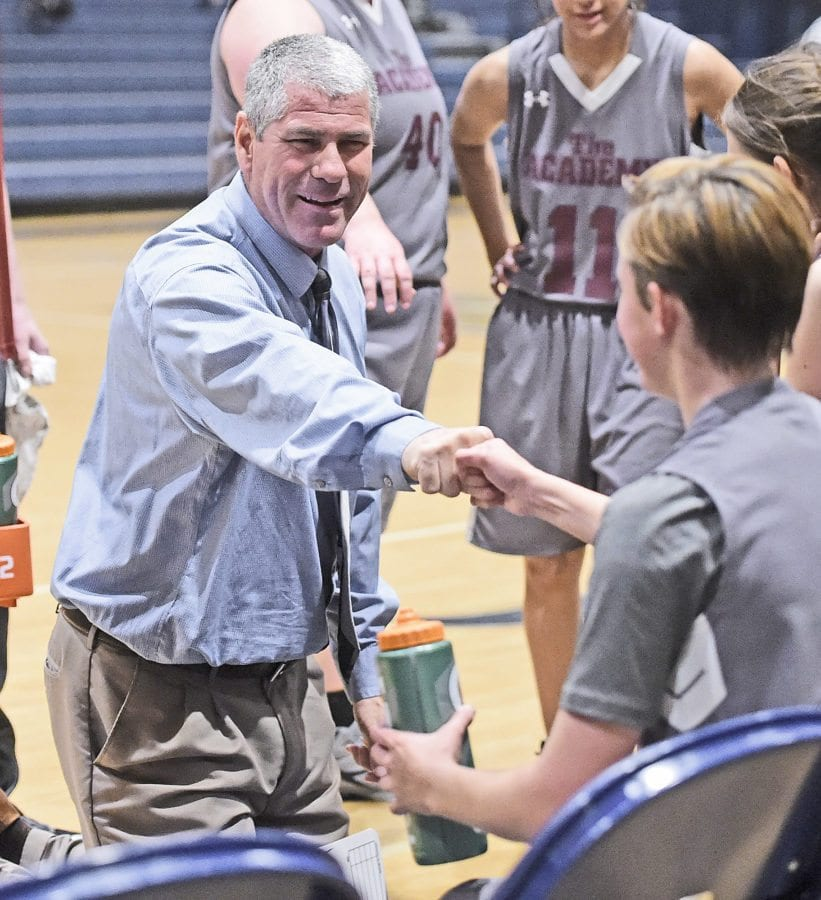 Einstein head coach Scott Barker, left, fist pumps with player Sam Sterba after she made a lay up against SCCS on Friday.  Dan Watson/the Signal