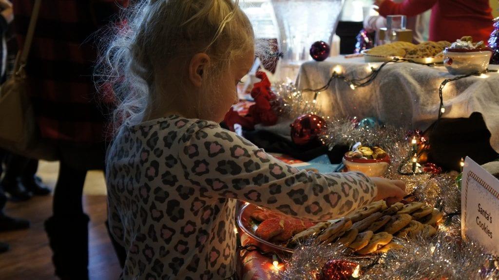 Alexa Brzozowski, 5, reaches for Santa's Cookies at Northpark Community Church on Sunday. Samie Gebers/ The Signal