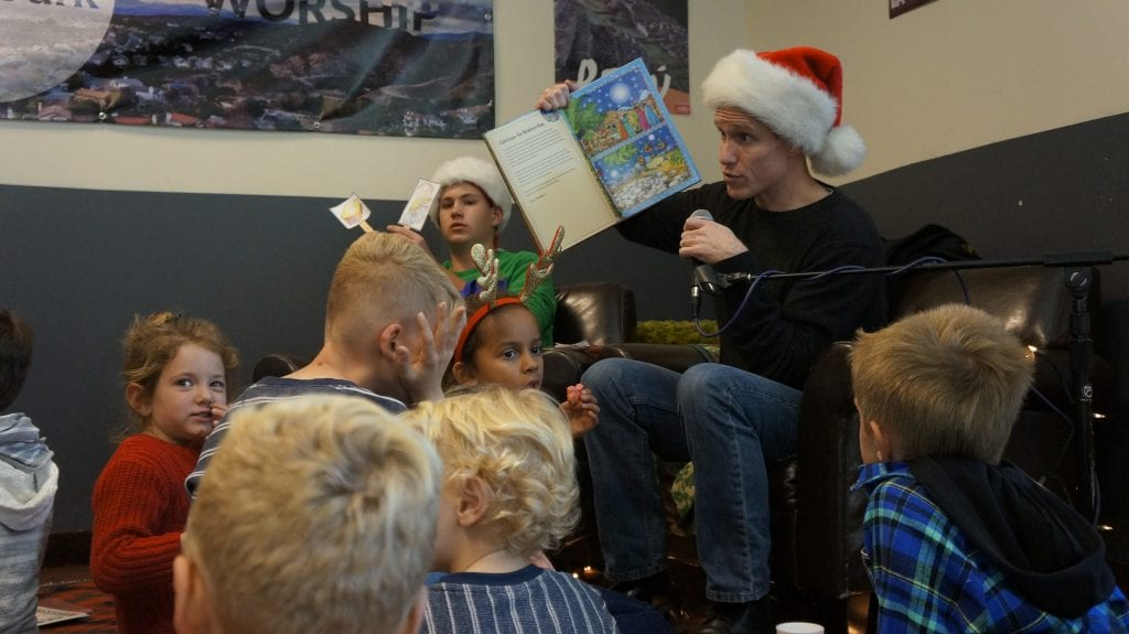 Pastor Robert Cavin reads Christmas Bible stories to children at the NorthPark Community Church on Sunday. Samie Gebers/ The Signal