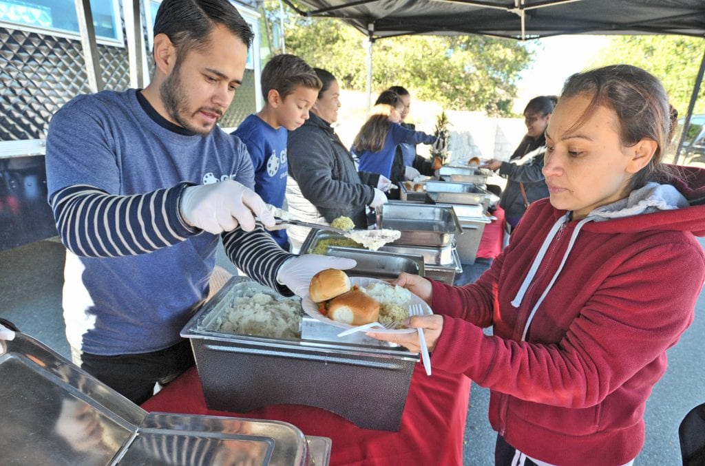 Volunteer Oscar Cervantes, left, serves mashed potatoes to some of the hundreds of attendees who enjoied a chicken dinner at the Festividad for Christ community event held at Faith Community Church in Newhall on Saturday. Dan Watson/The Signal