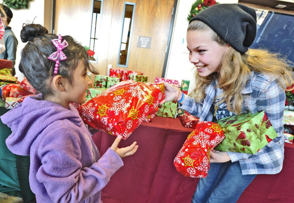 Yareni Galicia, 7, left, gets a gift from Sydney Jackson at the Festividad for Christ community event held at Faith Community Church in Newhall on Saturday. Dan Watson/The Signal