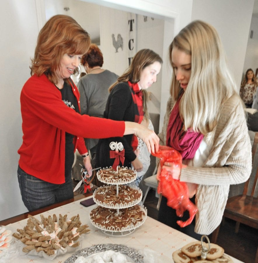 Wendy Stevenson. left, unwraps her desert as daughter, Grace places her grandmother's recipe for Almond English Toffee on the cookie table, representing three generations at Lynn Parkinson's 50th Annual Cookie Exchange in Sand Canyon on Saturday. Dan Watson/The Signal