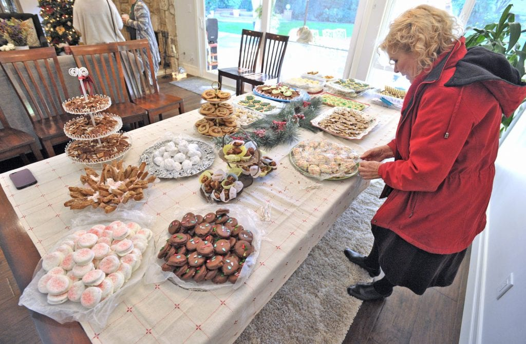 Evelyn Taibi places her four-dozens cookies on the table at Lynn Parkinson's 50th Annual Cookie Exchange in Sand Canyon on Saturday. Dan Watson/The Signal