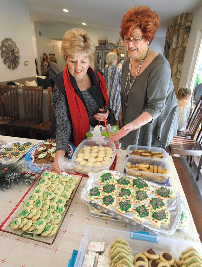 Lynn Parkinson, right, welcomes friend Leslie Christensen as she placers her four-dozens cookies on the table at Lynn Parkinson's 50th Annual Cookie Exchange in Sand Canyon on Saturday. Dan Watson/The Signal