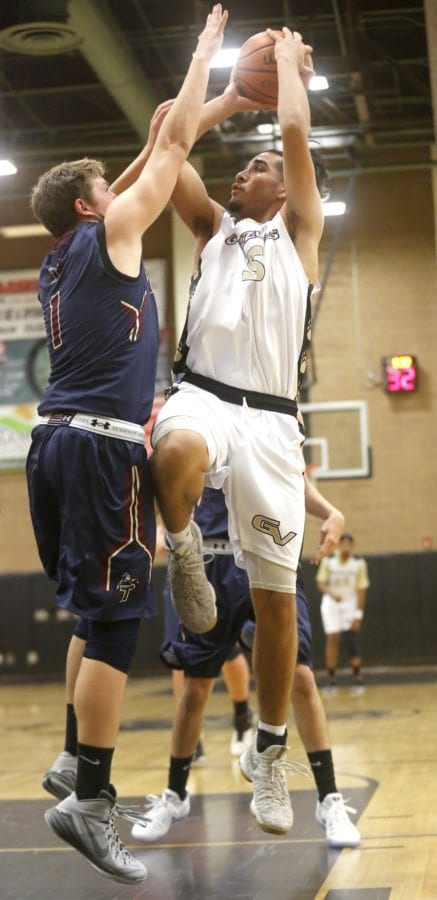 Golden Valley's Richard Kawakami (5) goes up for a shot as Trinity's Tyler Lee (1) tries to block him during a game at Golden Valley on Friday. Katharine Lotze/Signal