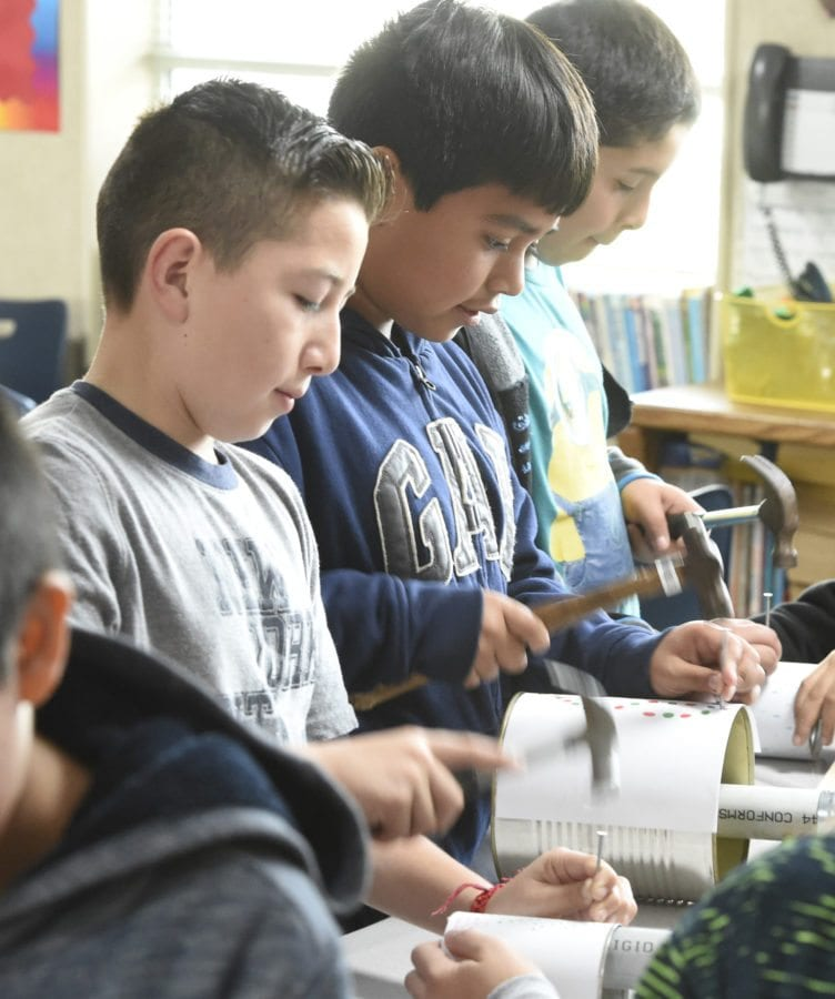 Fifth-graders from left, Victor Chinchilla, Byron Cardona and Steven Torres pound holes in tin cans as they make Colonial style candle lanterns as they  participate in the Colonial Day, fifth-grade learning event  at Newhall Elementary school in Newhall on Friday.  Dan Watson/The Signal