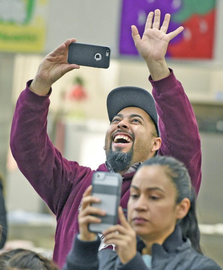 """Ruben Roparte waves to his child as 86 second-graders at Wiley Canyon Elementary School in Newhall present their show entitled """"Holiday Traditions Around The World"""" on Thursday.  Dan Watson/The Signal"""