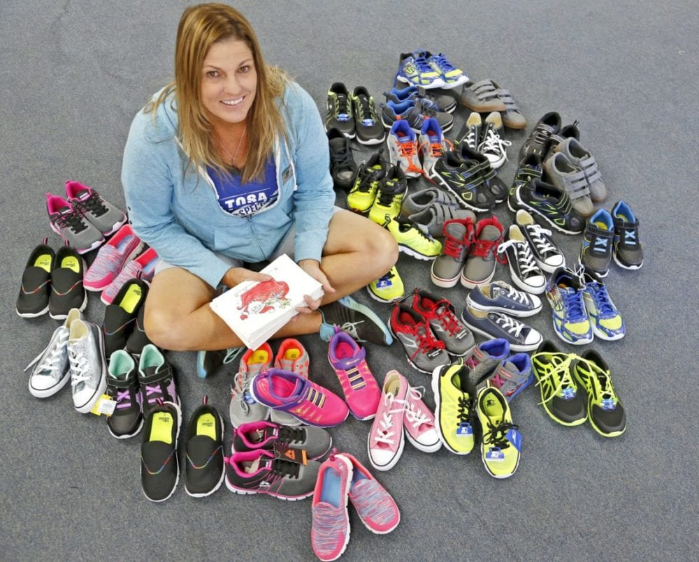 Saugus Union School District P.E. teacher Samantha Ford sits among the shoes she'll give out on Wednesday. Katharine Lotze/Signal